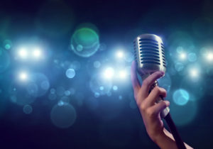 46501297 - close up of female hand on blurred background holding microphone